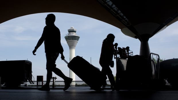 Passengers walk outside a departure hall at Kuala Lumpur International Airport on Saturday. Two air disasters within a year for Malaysia's national airline have had ramifications for airlines globally.