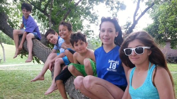 A group of youngsters pose on the limb of a tree in Regina Beach.