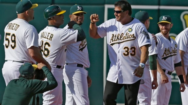 Former Oakland Athletic Jose Canseco (33) is welcomed by the team, including first base coach Tye Waller (46) during a pre-game ceremony on Saturday honouring the reunion of players from the 1989 world championship team.