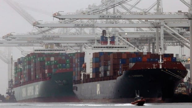 Container ships wait to be off-loaded. The IMF has downgraded its economic outlook for Canada and for the world.
