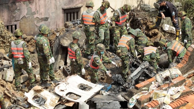 Soldiers remove debris from the TransAsia Airways flight GE222 crash site on the outlying Taiwanese island of Penghu, on July 25, 2014.