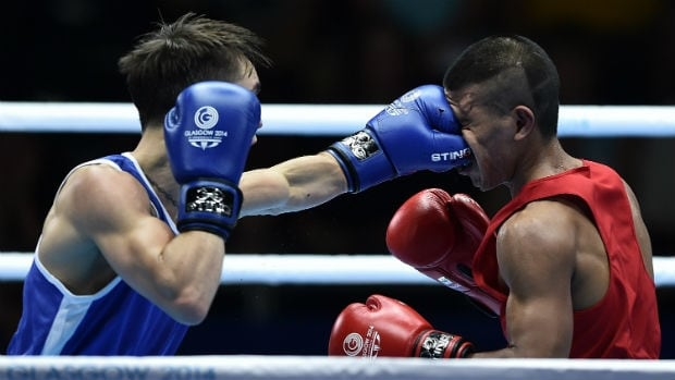 Northern Ireland's Michael Conlan, left, lands a punch to the face of Nauru's Mathew Martin during their bout at the Commonwealth Games on Friday.