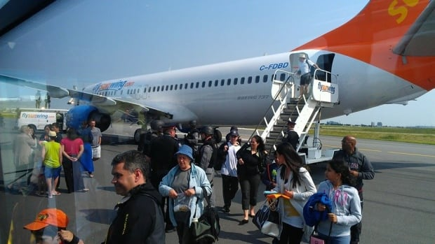 Passengers file out of Sunwing Flight 772