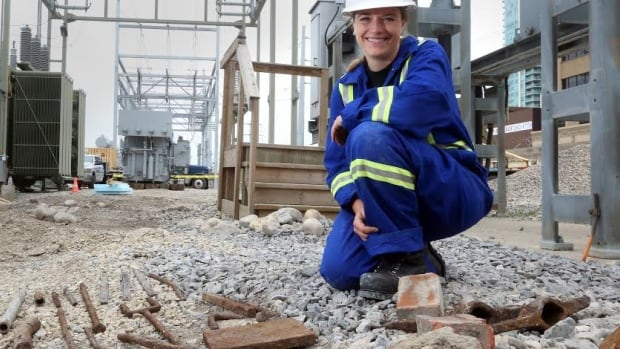 Michelle Wickham of Bison Historical Services Ltd. poses by railway artifacts unearthed during construction at ENMAX's downtown substation.