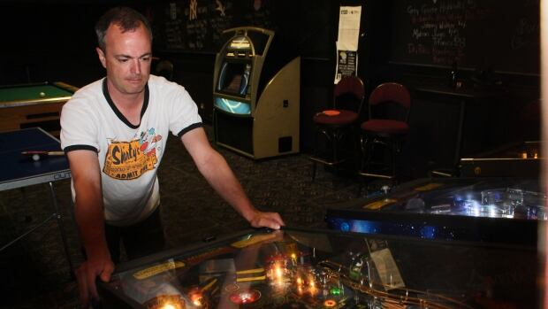 Jason Carroll, co-founder of the Saskatchewan Association of Pinball Players, playing at Sports on Tap.