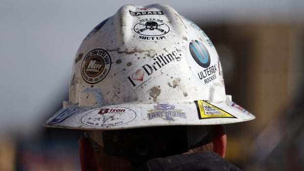 A worker wears a protective helmet decorated with stickers during a hydraulic fracturing operation at a gas well near Mead, Colo. Peter Hill, chairman of Denver-based Triangle Petroleum, says the industry could spur Nova Scotia's stalled economy and reduce its reliance on polluting and coal-fired plants.