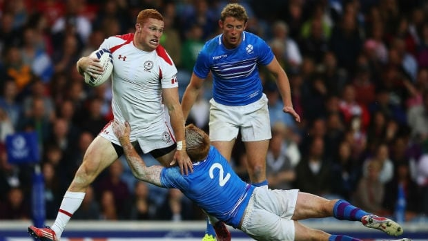 Michael Phillips of Canada, left, fights through a tackle during the team's rugby sevens group match at the Commonwealth Games.
