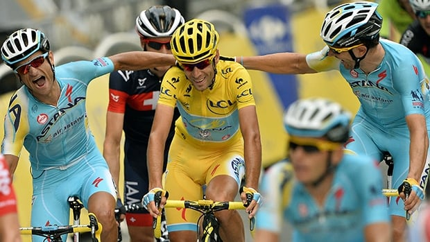 Tour de France winner Vincenzo Nibali, middle, is congratulated by teammates as he crosses the finish line in Paris on Sunday.