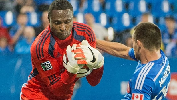 Impact Jack McInerney, right, bounces off of Portland Timbers goalie Donovan Ricketts as he makes a save Sunday in Montreal.