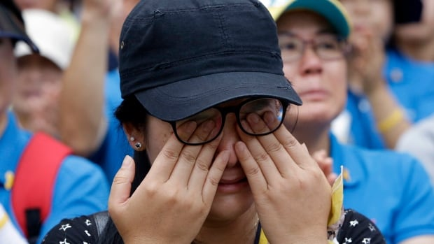 A family member of a victim of the sunken ferry Sewol wipes her tears during a rally 100 days after the ferry sunk. Survivors testified at the trial of 15 crew members Monday.