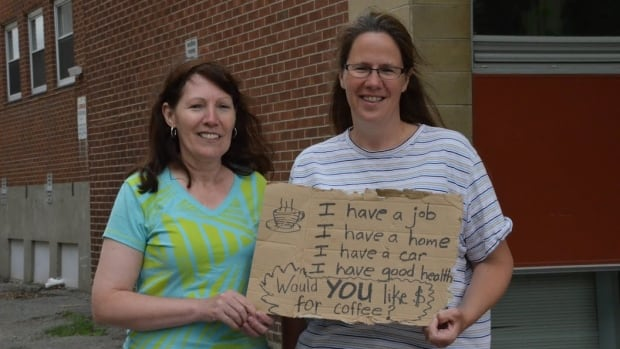 The pastor at Trinity United, Kathy Dahmer (right), wrote a poignant message down on a piece of cardboard and asked members of the church to take it downtown to see what happened. Congregation member Barb Cote (left) did just that.