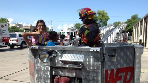 Vanessa Merkel 12, and Gideon Trout, 8, try out the ladder truck in Winnipeg at the kick-off to the 29th annual Firefighters Burn Camp, sponsored by the Firefighters Burn Fund Inc.