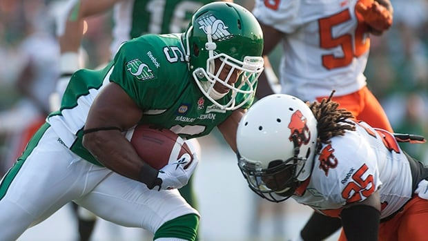 Roughriders running back Hugh Charles (5) collides with defensive back Ronnie Yell in a 26-13 loss to the Lions on July 12.