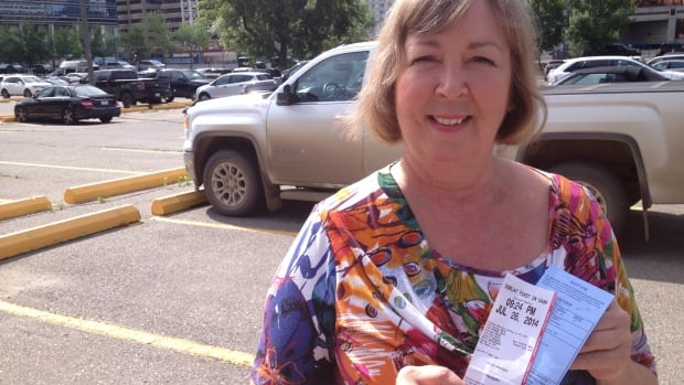 Pat Ruby holds up the $95 ticket she received last Saturday at an Impark parking lot located on Second Avenue southwest in Calgary.
