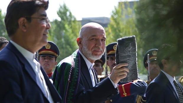Afghan President Hamid Karzai, centre, is shown leaving after Eid al-Fitr prayer at the presidential palace in Kabul on Monday. His cousin Hashmat Khalil Karzai was assassinated by a suicide bomber on Tuesday.