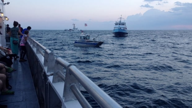 A whale watching ship (foreground), stranded 20 miles off the coast of Boston,  is pictured early Tuesday June 29, 2014. The Boston Harbor Cruises whale watch vessel was freed Tuesday and docked at Boston's Long Wharf shortly after 8 a.m., some 17 hours after the voyage began.