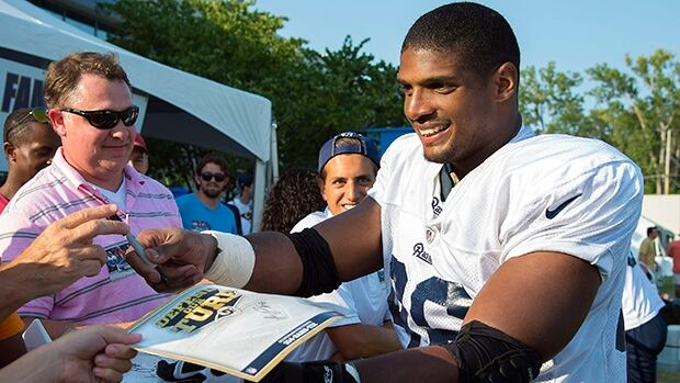 Rams rookie defensive lineman Michael Sam (96) signs autographs following practice at Rams Park in St. Louis on Tuesday.