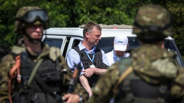 Alexander Hug, deputy head for the Organization for Security and Co-operation in Europe's monitoring mission in Ukraine, looks on next to armed pro-Russian separatists on the way to the site in eastern Ukraine where the downed Malaysia Airlines flight MH17 crashed. OSCE never reached the site.