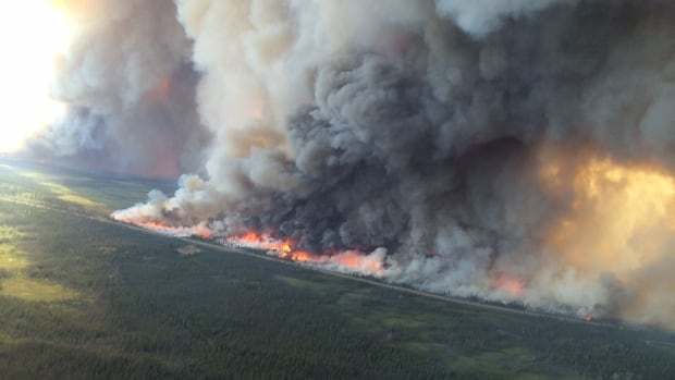 Fire crews conduct controlled burns along Highway 3 between Behchoko and Fort Providence, N.W.T., earlier this summer. N.W.T.'s Department of Environment and Natural Resources says strong winds caused part of the Birch Lake Complex, a massive 650,000 hectare fire along Highway 3, to jump across a bay near Moraine Point Lodge Saturday afternoon.