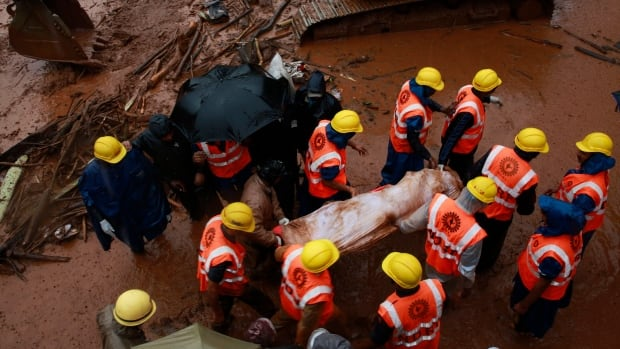 Rescue workers carry the body of a victim after a massive landslide in Malin village in Pune district of western Maharashtra state, India, on Thursday.