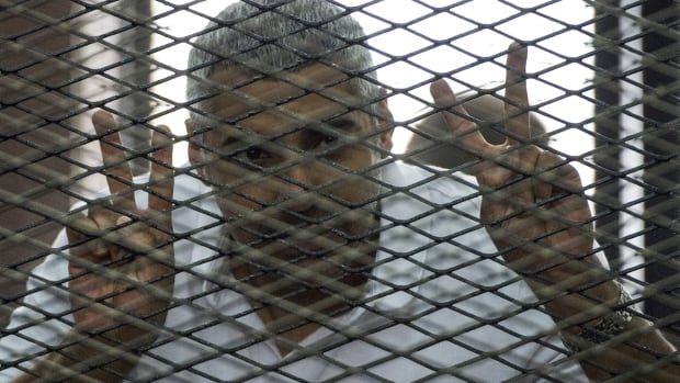Egyptian-Canadian Mohamed Fadel Fahmy listens to his verdict inside the defendants cage. He calls the court's decisions a farce.