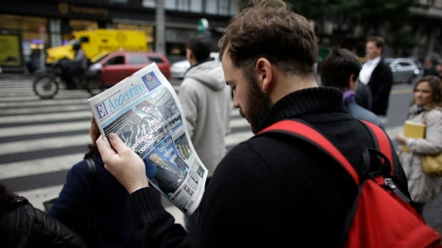 A man reads a newspaper with a headline that reads in Spanish, 'Argentina Didn't Accept the Conditions of the Vultures,' referring to U.S. hedge funds.