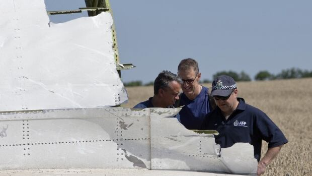 Australian and Dutch experts examine a piece of the Malaysia Airlines Flight MH17 plane on Friday.
