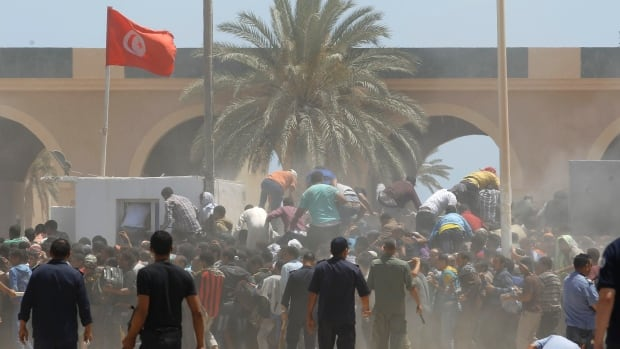 Tunisian guards confront a group of Egyptians at the border crossing of Ras Jdir, southeast of Tunis, on Friday. Tunisian guards shot into the air and fired tear gas to stop a group of Egyptians from storming across the border with Libya after fleeing violence in Tripoli, a Reuters reporter said.