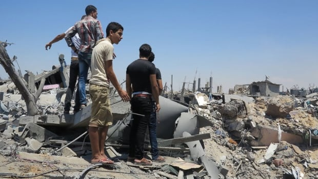 A group of young men survey the damage in Shejeia.
