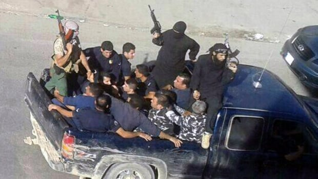 Gunmen drive away with about a dozen men, two in camouflage police uniforms, in Arsal, a Sunni Muslim town near the Syrian border in eastern Lebanon.