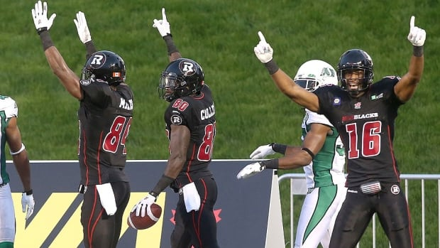 Redblacks receiver Dobson Collins (80) celebrates his touchdown with teammates Wallace Miles (84) and Marcus Henry (16) as Roughriders cornerback Tyron Brackenridge (41) looks on Saturday night in Ottawa. Collins recovered the football in the end zone on a pooch punt for the team's first-ever touchdown at home.