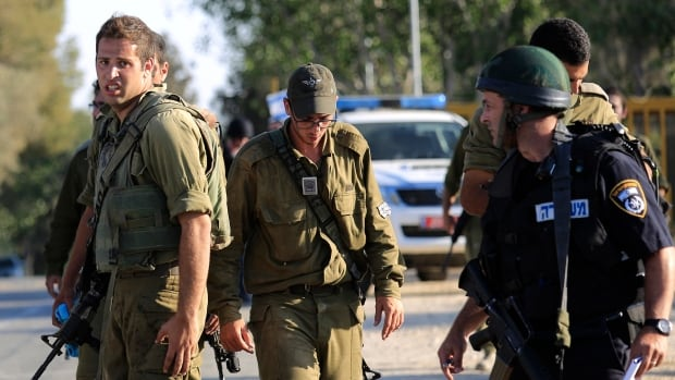 Israeli solders and police at the site near the Israeli-Gaza border where a man was injured from a mortar shell fired from the Gaza Strip on Sunday. Later, Israel said its military would hold a seven-hour humanitarian truce, starting at 3 a.m. ET, on Monday, but would fight back if attacked.