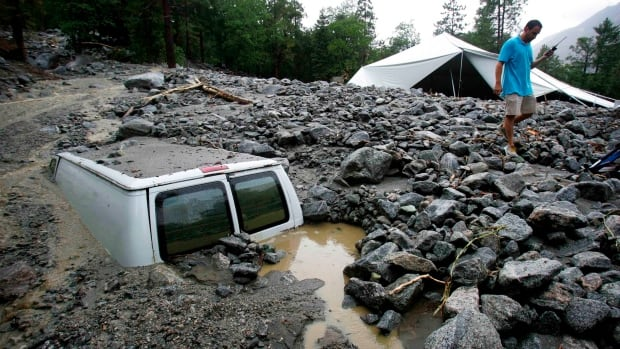About 2,000 people in two separate towns are stranded after mudslides covered mountain roads with debris Sunday.