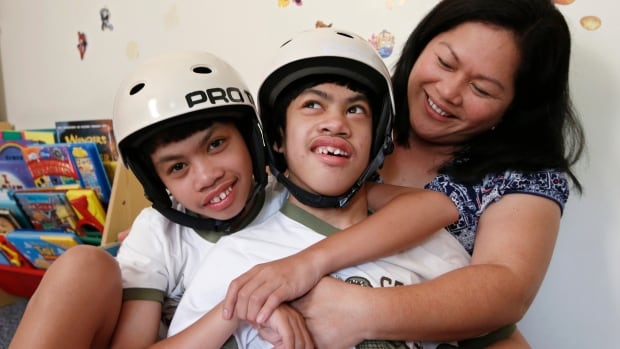 Formerly conjoined twins Clarence, left, and Carl Aguirre, 12, embrace while relaxing with their mother Arlene at the family's home in Scarsdale, N.Y. On Aug. 4, the family celebrated the 10th anniversary of the surgery that separated the twins.