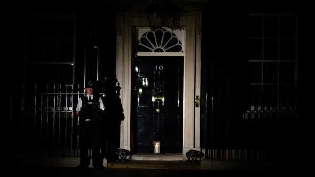 A policeman stands guard as a lantern is placed at the front door of No. 10 Downing Street, the British Prime Minister's London residence, during a lights-out commemoration to mark the 100th anniversary of the outbreak of the First World War.