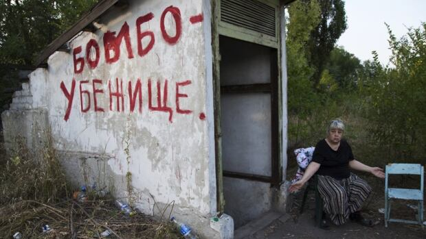 """A resident of Ukraine sits near an entrance with """"Bomb Shelter"""" written on the side, as she waits for shelling to start. Many Thunder Bay residents are concerned about the tragic events unfolding in that country."""
