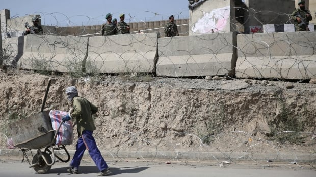 An Afghan laborer walks past a gate of Camp Qargha on Aug. 5, 2014.  In a statement NATO said it was investigating an 'incident' involving both Afghan and international troops at Camp Qargha, which trains officers for the country's army.