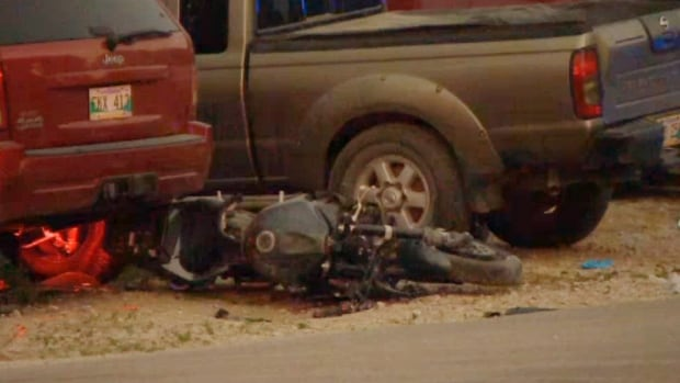 A motorcycle lies on the ground after crashing into a parked vehicle on Sunday evening north of Winnipeg.