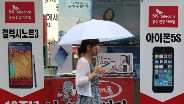 A woman in South Korea walks by ads for Samsung Electronics' Galaxy Note III, left, and Apple's iPhone 5s. Samsung and Apple Inc. have agreed to end all patent lawsuits between each other outside the U.S.