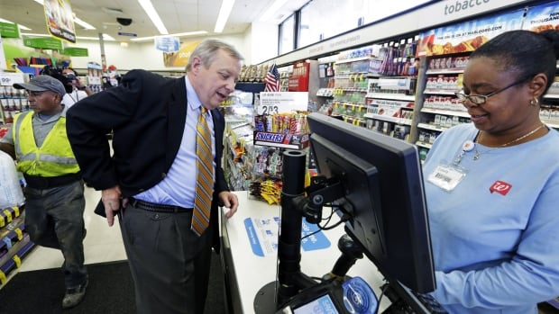 U.S. Sen. Dick Durbin, D-Ill., shops at a Walgreen after praising the chain for declining to pursue an overseas reorganization to trim its U.S. taxes.