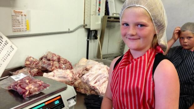 Emma Covlin, 8, weighing and pricing chicken parts in her family's butcher shop on their farm near Endeavour, Sask.