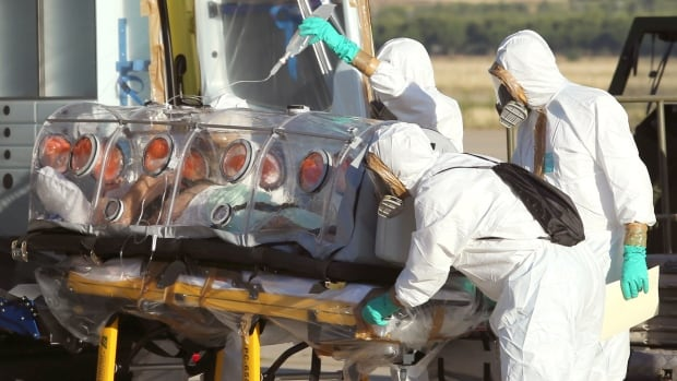 Aid workers and doctors transfer Miguel Pajares, a Spanish priest infected with the Ebola virus, to an ambulance after flying him home. A B.C. company, Tekmira has approval from the USFDA for use of its early stage drug on infected people.