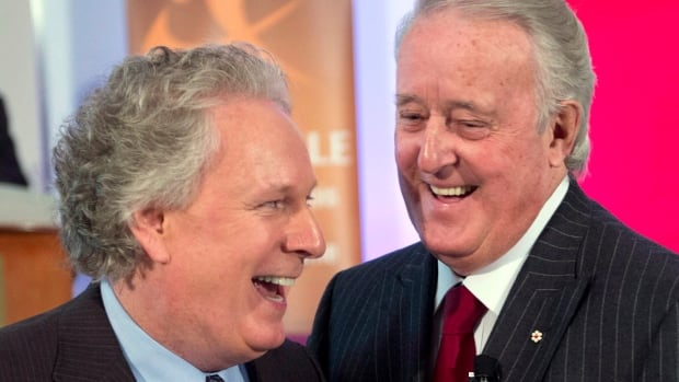 Former Prime Minister Brian Mulroney, right, arrives with former Quebec Premier Jean Charest at an event last February. On CBC Daybreak on Aug. 7, Charest said it was unlikely he'd return to politics but he never says never.