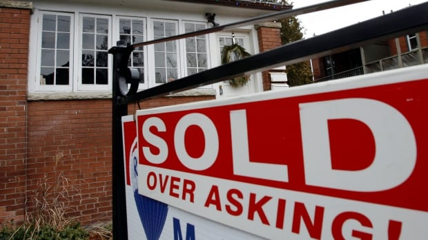 A sold sign is displayed in front of a home in Toronto, where the number of home resales in July surged 10 per cent from the same month a year earlier.