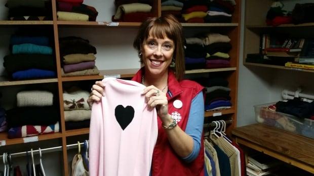 Do Crew volunteer Johanne Vincent takes a break, from folding sweaters at Chez Doris, to smile for the camera. (Photo: Johanna Tzountzouris, CBC communications)