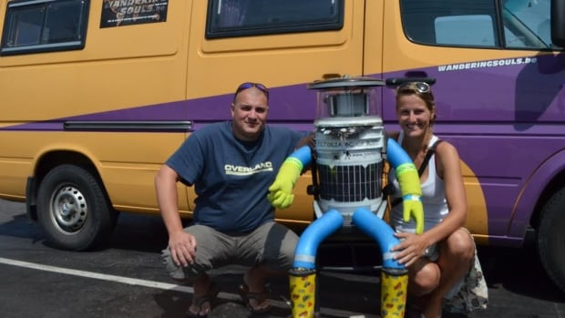 Belgian tourists Seb Leeson and Kim Van Aerde pose with the Canadian hitchiking robot known as HitchBOT. On Thursday, the robot made it halfway in its country-wide trek.