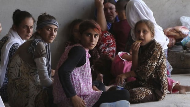 Women and children from the minority Yazidi sect flee the violence in the Iraqi town of Sinjar, west of Mosul.