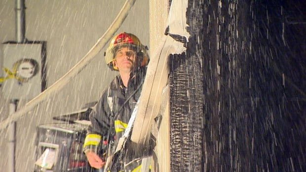 A Vancouver firefighter stands behind a wall of water early Thursday morning as another douses a garage rooftop fire that police say was deliberately set. Vancouver police are investigating whether this is linked to ongoing violence in the city's South Slope neighbourhood.