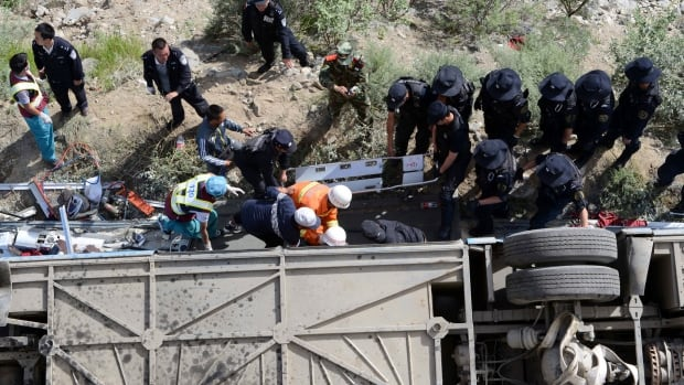 Rescuers try to pull survivors from an overturned tour bus after it fell off a 10-metre cliff in Tibet.