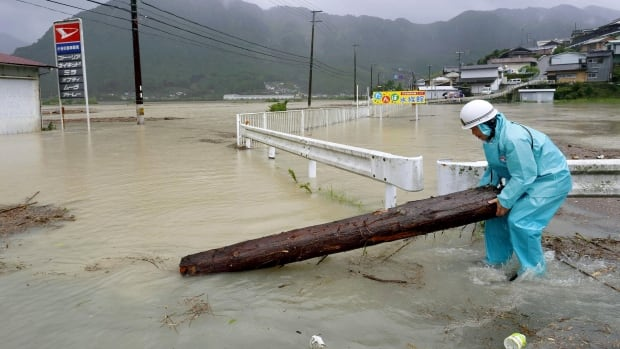A worker takes a driftwood away from a road flooded by a swollen river in Shingu, western Japan. The storm prompted evacuation alerts for about 1.2 million people near swollen rivers.